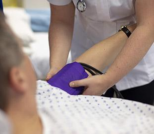 Nurse fixing a blood pressure sleeve to an arm