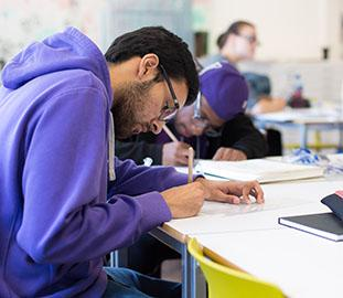 students writing at a desk