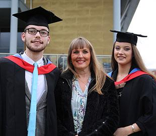 Two students in graduation robes aside a mature woman