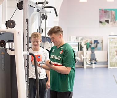 two young men beside gym equipment
