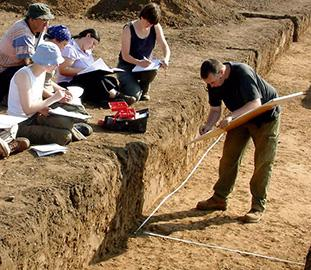 students writing notes beside a trench