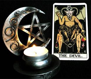 tarot card of the devil beside a star a moon and a candle